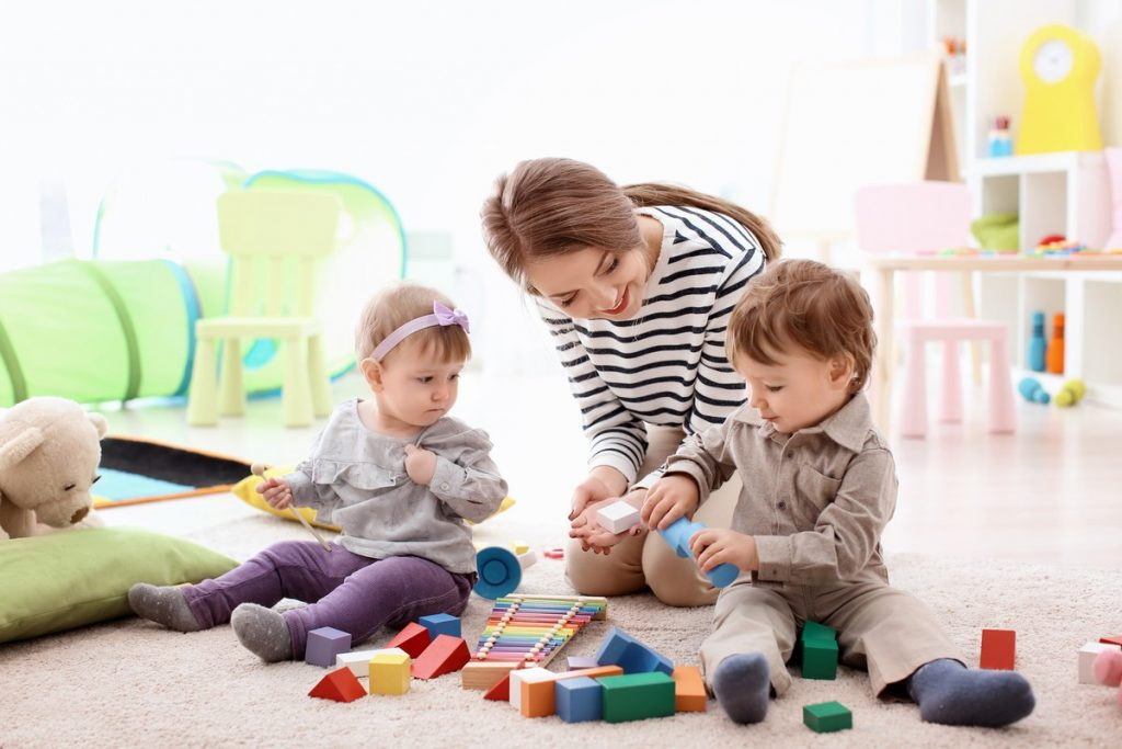 young nanny playing with little children