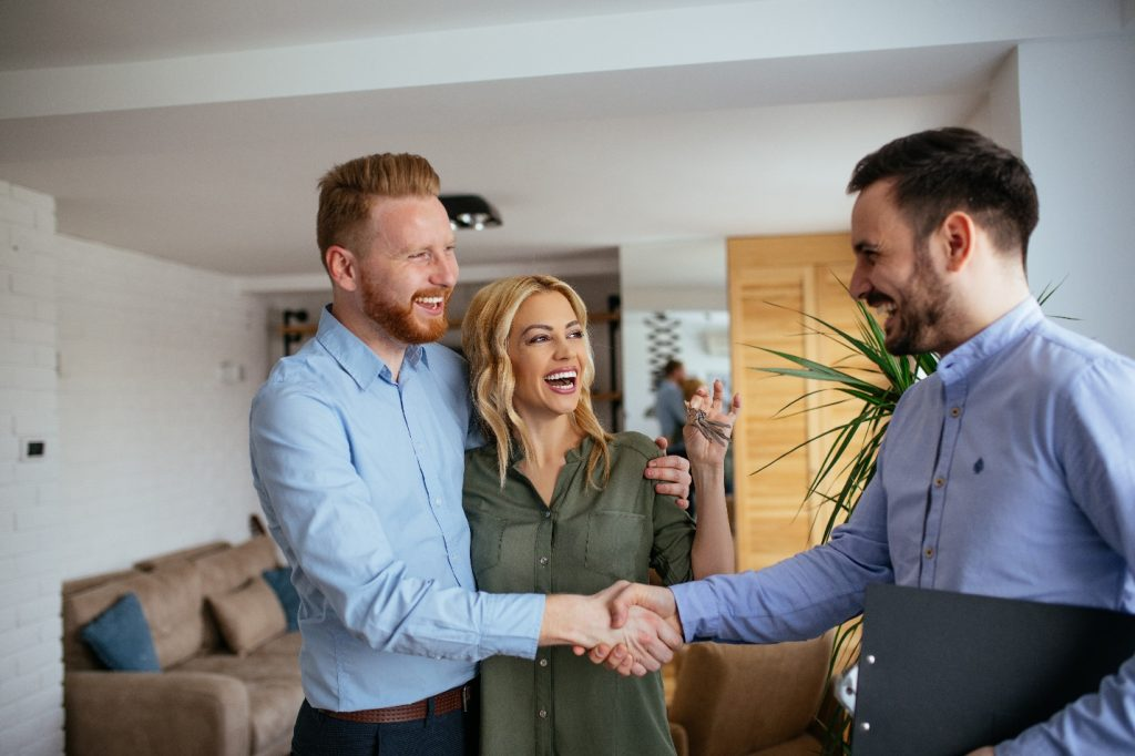 financial adviser congratulating to a young couple for buying a new house