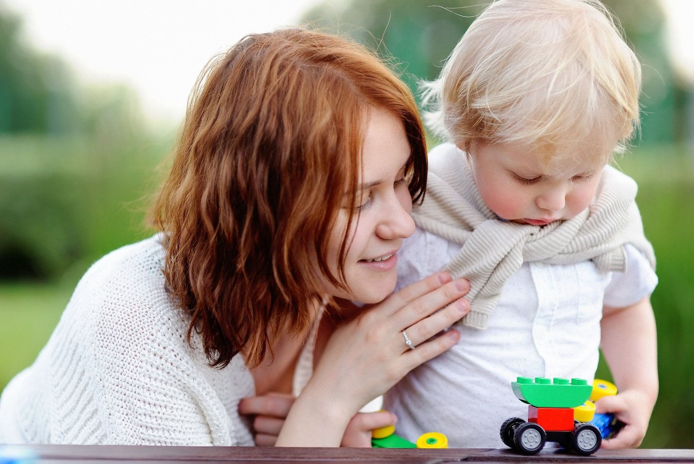 young woman with his toddler son playing with colorful blocks