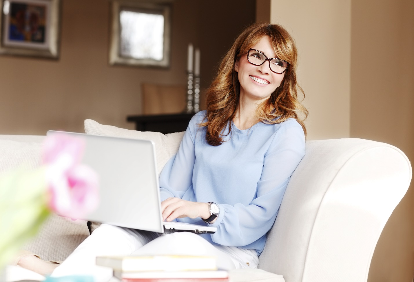 happy beautiful woman sitting at living room and using her laptop