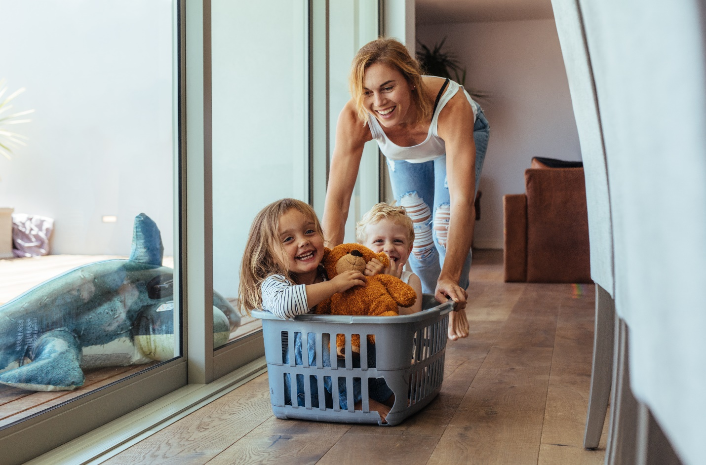 happy young mother pushing children sitting in laundry basket