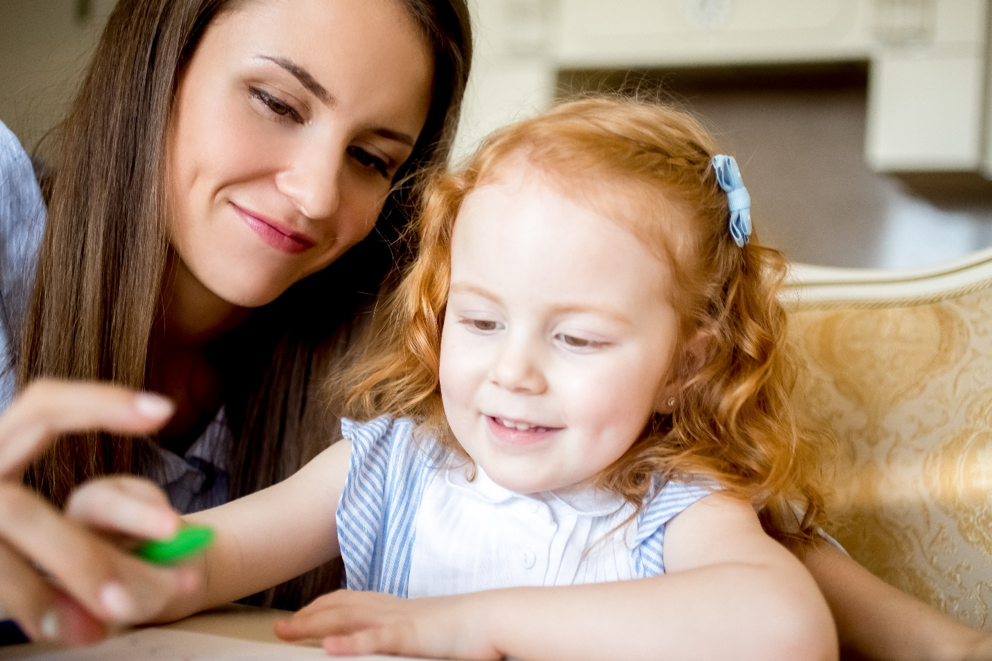 cheerful little girl drawing with mother or nanny