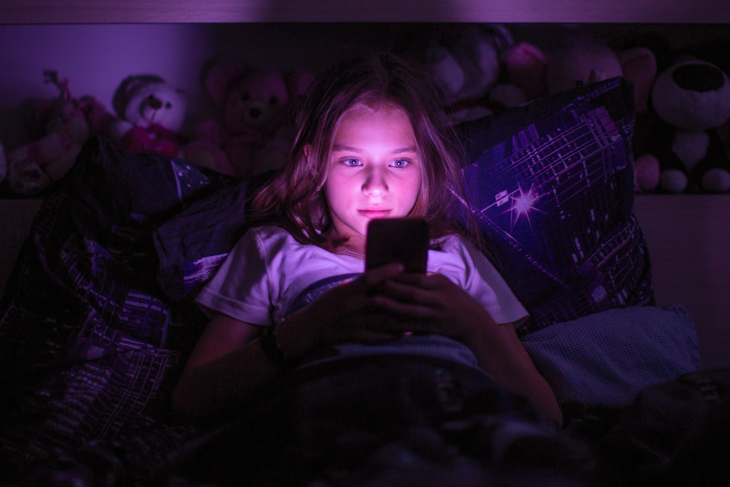 little girl lying under a blanket looking at the smartphone at night