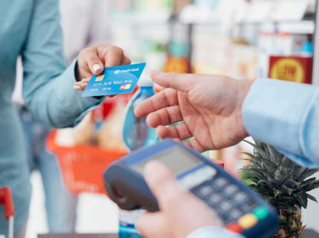 Woman at the supermarket checkout and paying using a credit card