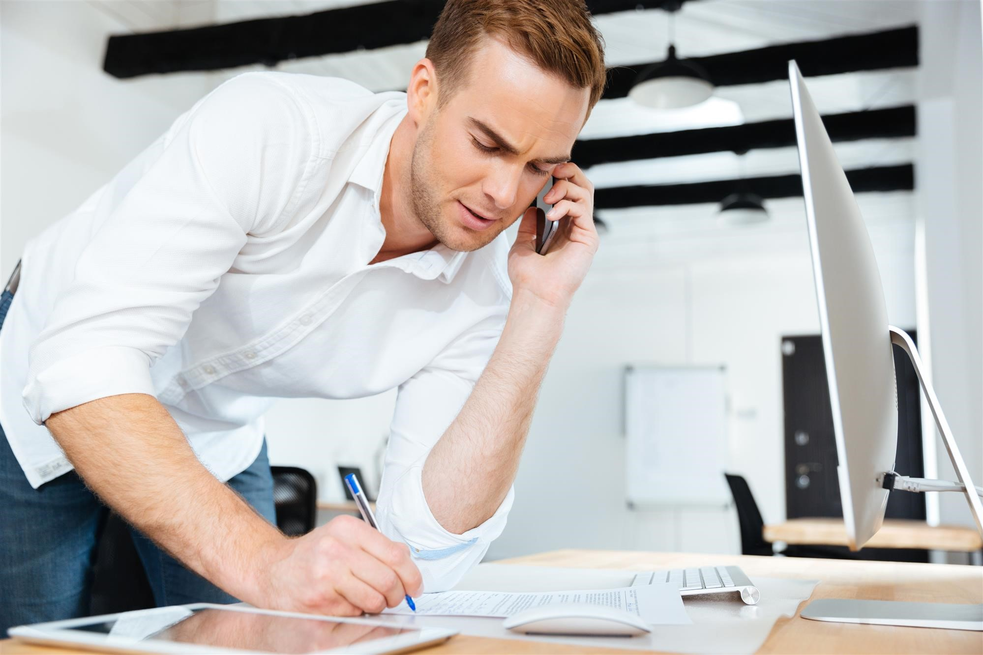 Handsome young businessman talking on cell phone and writing in office