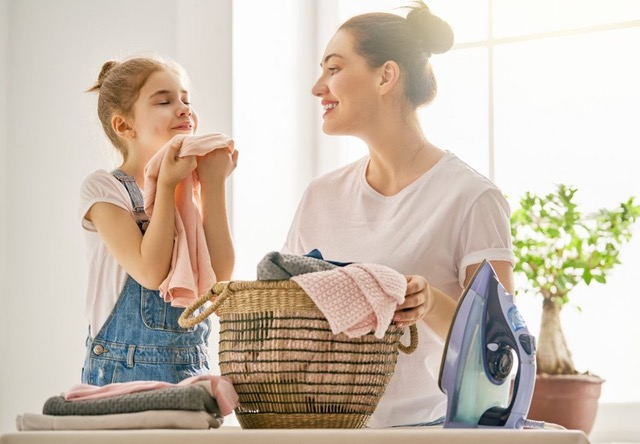 Beautiful young woman and child girl having fun and smiling while ironing at home.