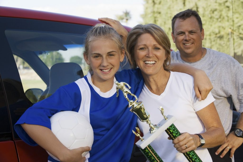happy parents with daughter holding soccer trophy
