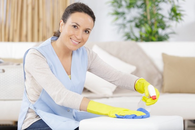 woman housekeeper holding cleaning products in kitchen