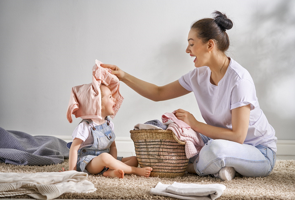 Beautiful young woman and child girl are having fun and smiling while doing laundry at home.