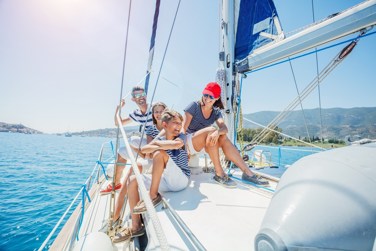 Happy Family with adorable kids resting on yacht
