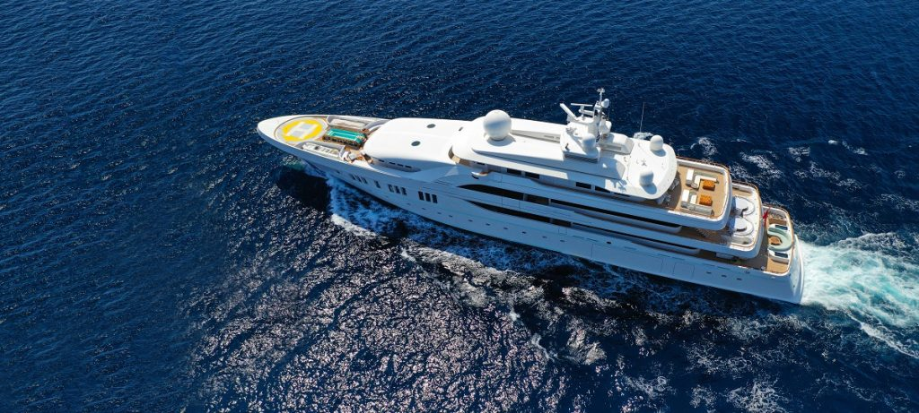 Aerial view of luxury mega yacht with wooden deck cruising Aegean deep blue sea