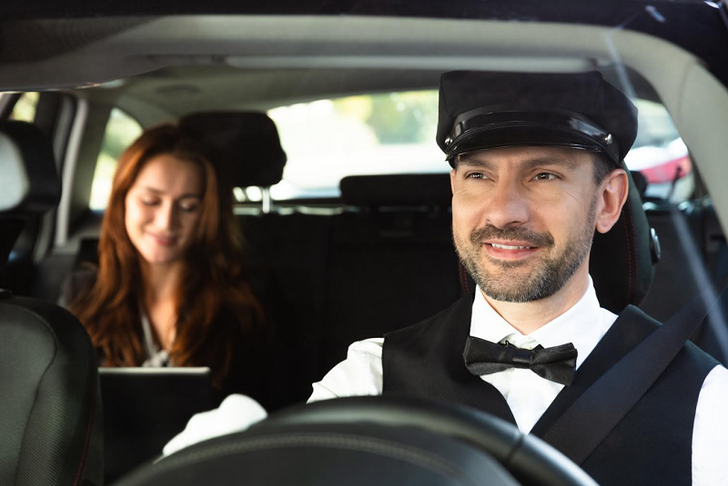 Businesswoman Sitting Behind Happy Male Chauffeur Driving Car