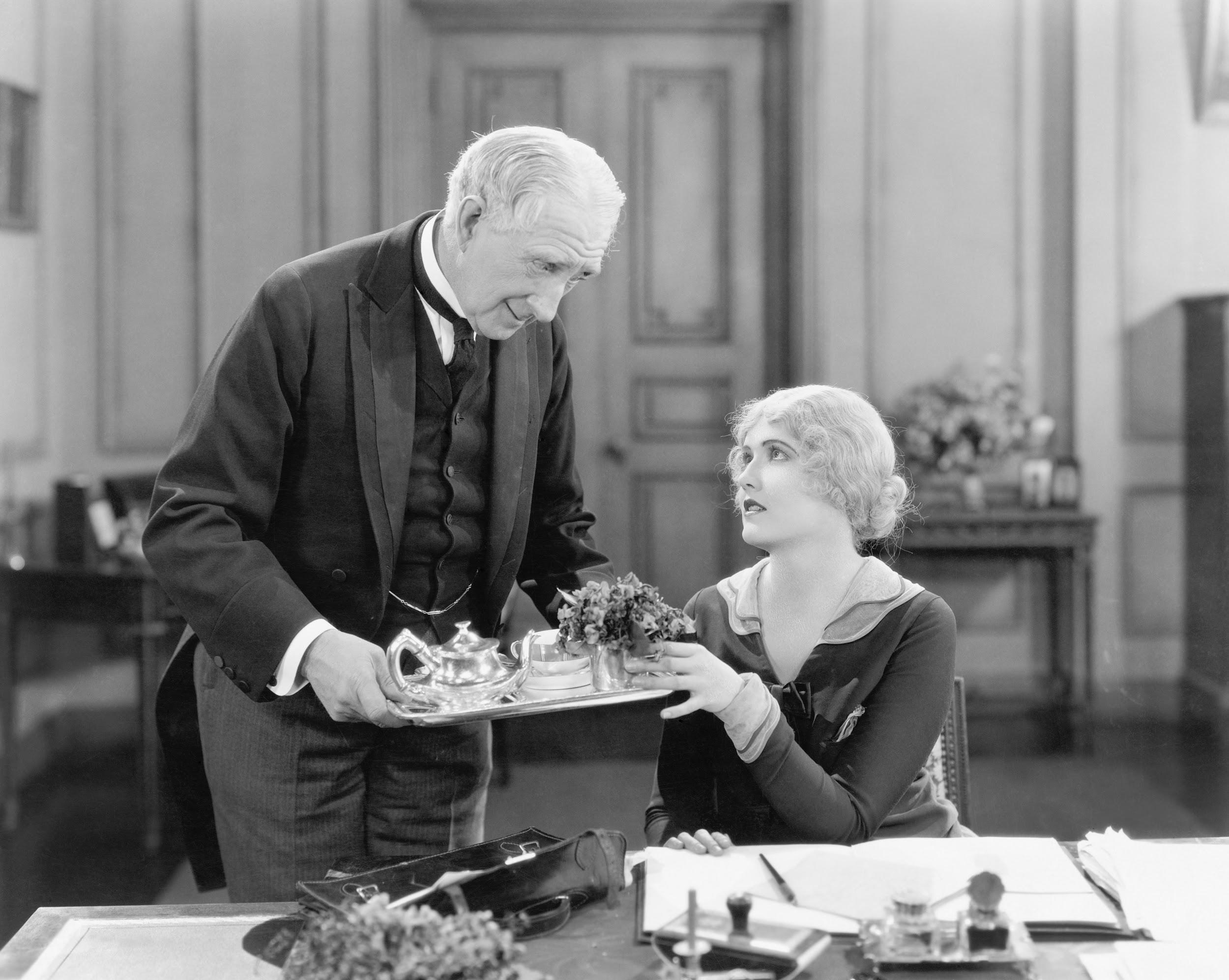 Older man serving a woman tea on a tray