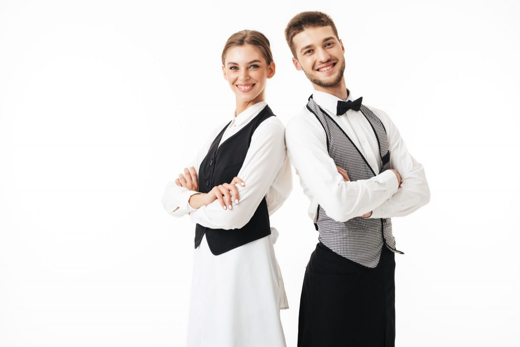 Young smiling waiter and waitress in white shirts and vests standing back to back