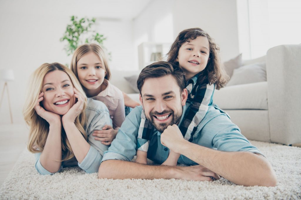 four members family lying floor toothy smiling fluffy carpet cozy apartments