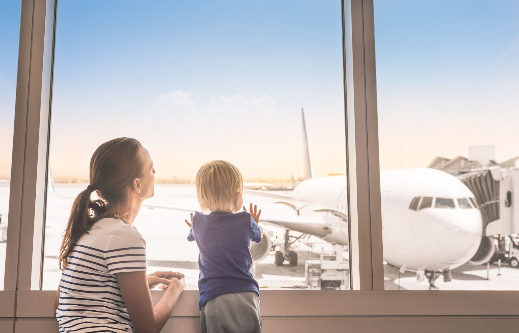 Mother and son at airport looking out window at airplane