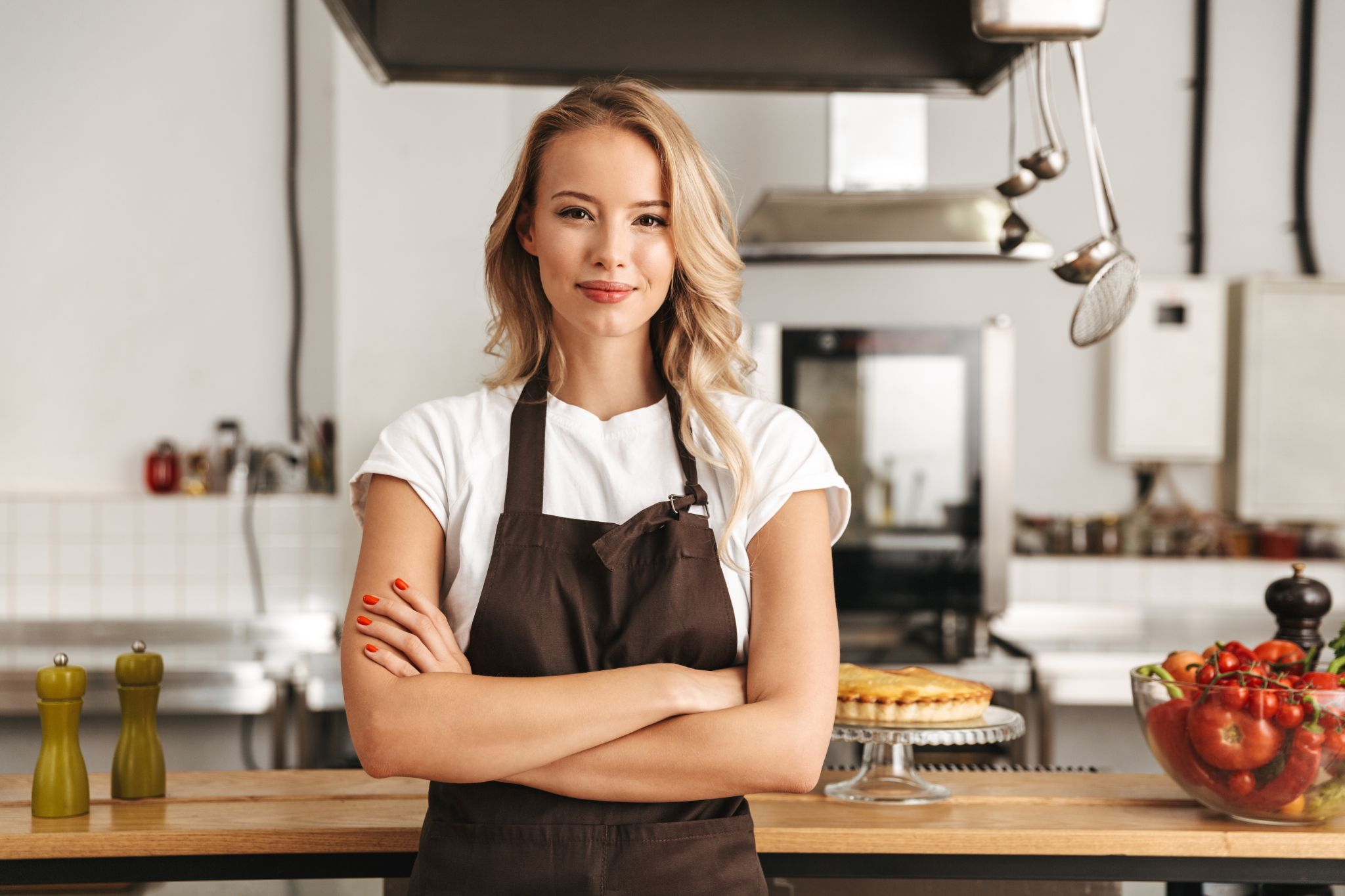Smiling young woman chef in apron standing at the kitchen