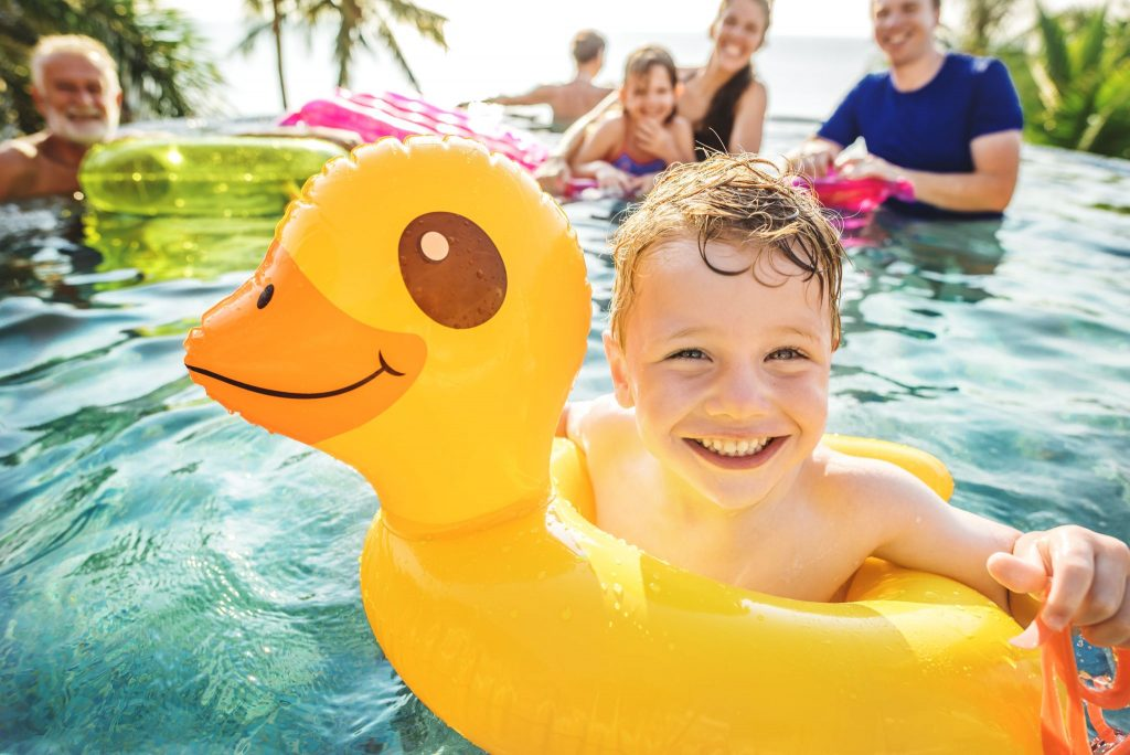 boy swimming in a pool with family