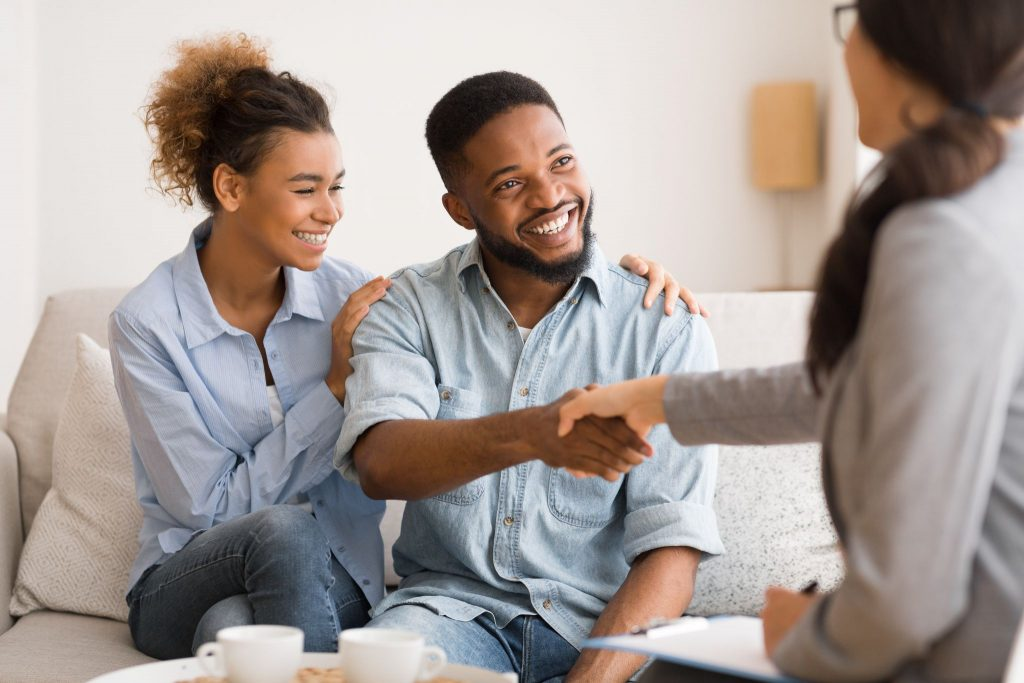 Cheerful young afro couple handshaking with marital therapist after session