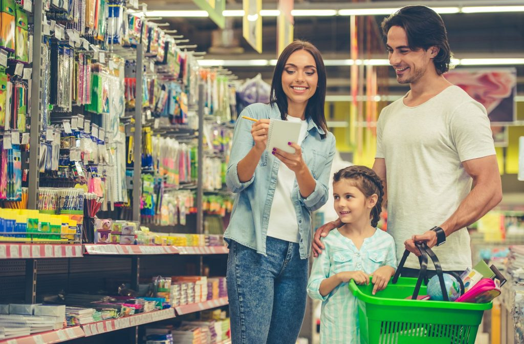 young parents and their little daughter are smiling while choosing school stationery in the supermarket.