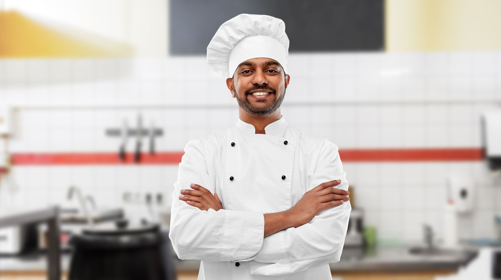 happy male indian chef in toque with crossed arms over restaurant kitchen background