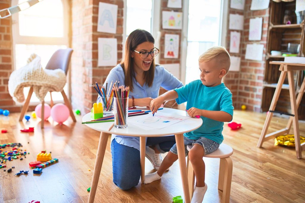 Young child playing at playschool with teacher
